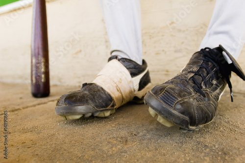 Baseball player sitting, close-up of baseball shoes, low section