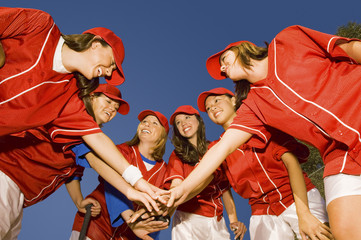 Women's softball team in huddle, low angle view