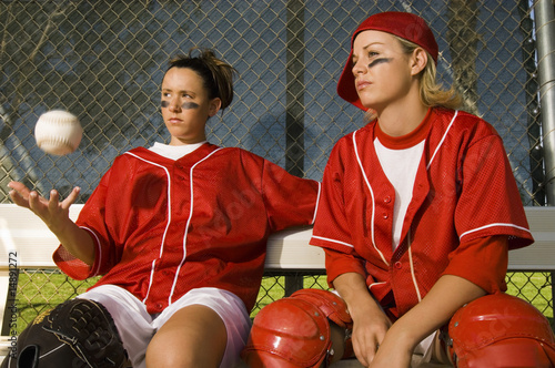 Softball players sitting on bench, portrait