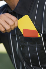 Referee taking card from pocket, mid section