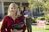 Portrait of smiling estate agent with house and home buyers in background