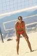 Female beach volleyball player bending down, hand on knees, waiting for serve