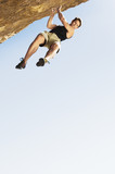 Climber Jumping off Cliff, low angle view