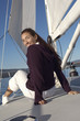 Young woman sitting on deck of sailboat, portrait