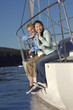 Young couple sitting on side of sailboat, portrait