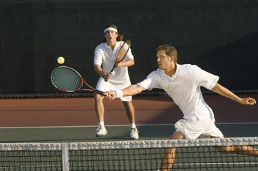 Tennis Player stretching, Swinging at Ball near tennis net, doubles partner standing behind