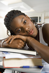 Young woman resting on stacked books, close-up, portrait