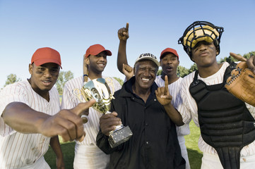 Baseball team and coach celebrating victory, outdoors, portrait