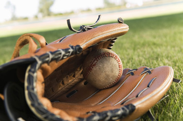 Baseball glove and ball on field, close-up