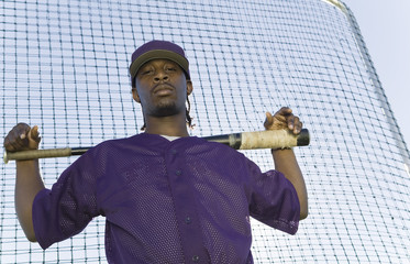Baseball player holding bat during practice, portrait