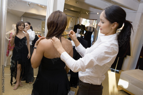 Saleswoman assisting customer with dress, side view