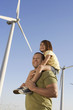 Father and daughter 5-6 on wind farm, side view