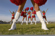 Cheerleader in white knee high boots, low section with cheerleaders behind