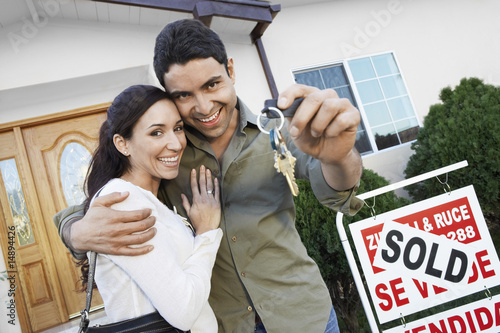 Homeowners standing in front of house with Sold sign holding key, portrait