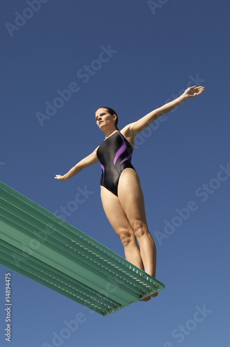 Woman about to dive backwards off a diving board