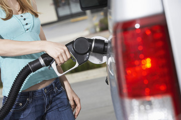 Young woman filling car with gas at gas station, mid section