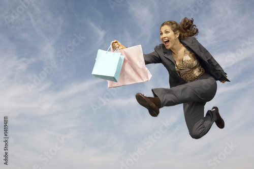Woman running with shopping bags mid-air outdoors