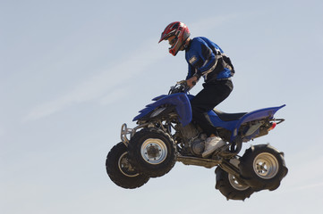Man riding quad bike in mid-air against blue sky, close up