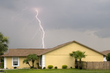 Daytime lightning strike near homes during afternoon storm poster