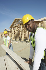 Construction Workers Stacking Timber