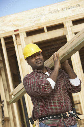 Construction Worker Carrying Lumber