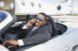 Man sitting in Convertible near private jet, talking on mobile