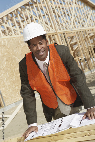 Surveyor Reading Blueprints on Construction Site