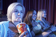 Young woman drinking soft drink, sitting with Friends, Watching Movie in theatre