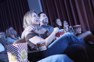 Smiling Couple sitting, arms around, Watching Movie in theatre
