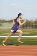 Female athlete running, side view