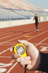 Man holding stopwatch, close up of hand, timing runner on running track