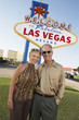 Couple in front of Welcome to Las Vegas sign, portrait