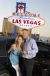 Couple getting out of limousine, man holding empty glass, in front of Welcome to Las Vegas sign
