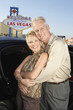 Mature couple in front of car and Welcome to Las Vegas sign