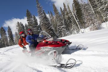 Couple driving snowmobile through snow