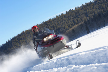Man Snowmobiling through snow in front of forest, low angle view.