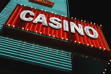 Neon casino sign at night, low angle view