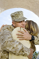 Soldier embracing wife, outdoors