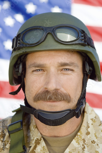 Soldier with moustache in front of United States flag, close-up, portrait