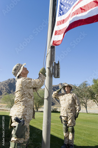 Soldiers raising United States flag, outdoors