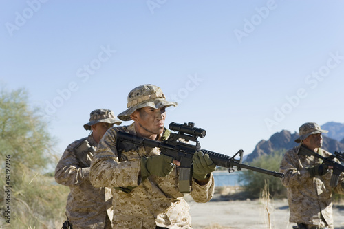 Soldiers carrying rifles in the field