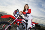 Female motocross racer on bike in desert, portrait