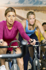 Woman using exercise bikes, indoors