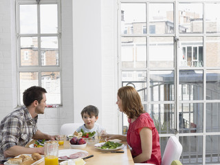 Boy 5-6 eating lunch with parents at dining room table