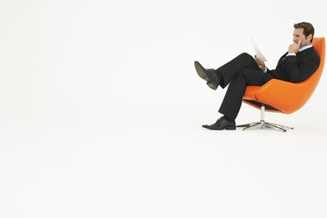 Businessman reading in chair, on white background
