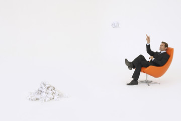 Businessman throwing piece of crumpled paper on pile
