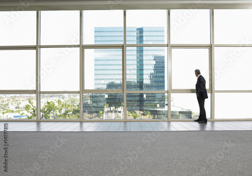 Businessman by window in office building