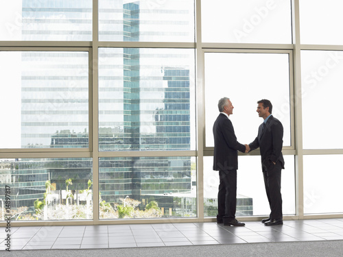 Businessmen shaking hands in office building