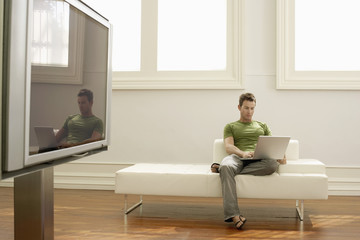 Man using laptop on modern sofa in modern apartment