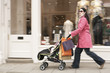 Mother pushing stroller by clothes shop on street